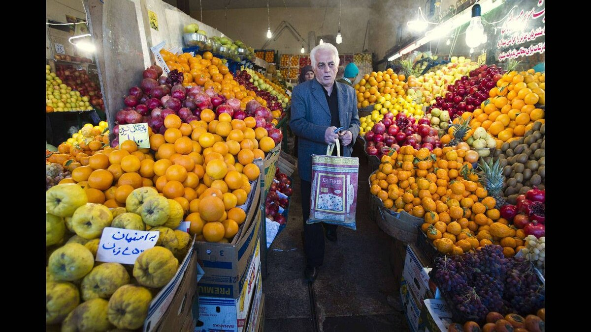 A man leaves after shopping at a fruit store in Tehran January 6, 2012.