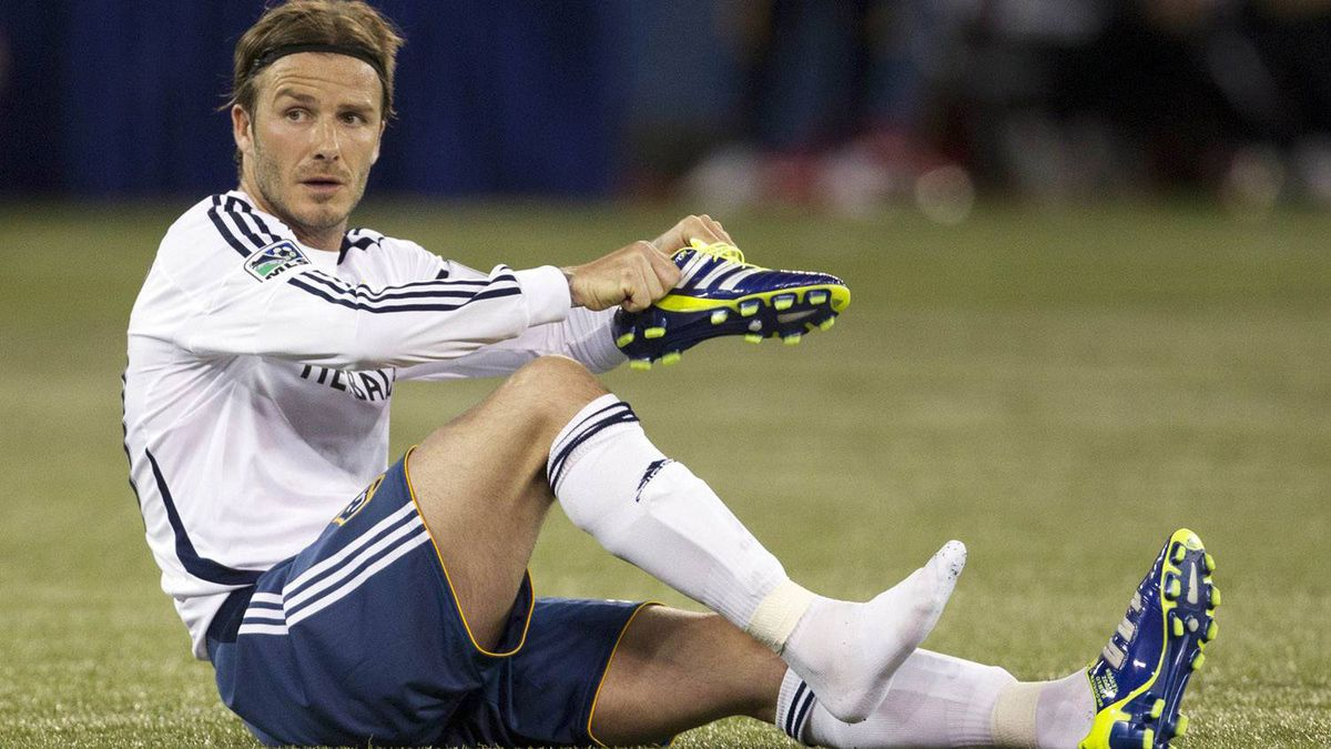 David Beckham removes his boot during a break in play in the second half.