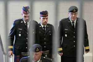Cpl. Matthew Wilcox, the 24-year-old soldier from Glace Bay, N.S., who was convicted in July of criminal negligence causing death and neglect of duty, is framed by a railing as he is escorted from his sentencing hearing in Sydney, N.S. on Friday, Sept. 11, 2009.