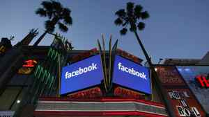 """Screens outside the Grauman's Chinese Theatre on Hollywood Blvd. advertise for people to """"Become a Fan"""" of the theatre on Facebook in Los Angeles, Monday, May 14, 2012."""