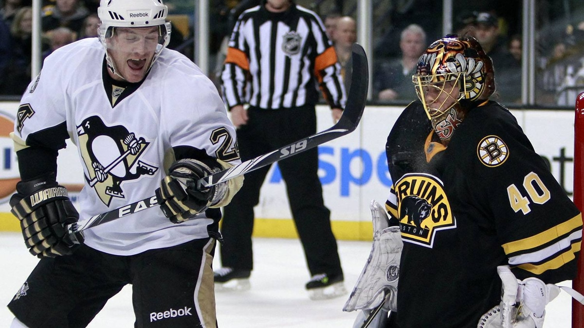 Boston Bruins goalie Tuukka Rask (40), of Finland, blocks a shot on his chest in front of Pittsburgh Penguins' Matt Cooke in the first period of an NHL hockey game, Saturday, Jan. 15, 2011, in Boston. (AP Photo/Michael Dwyer)