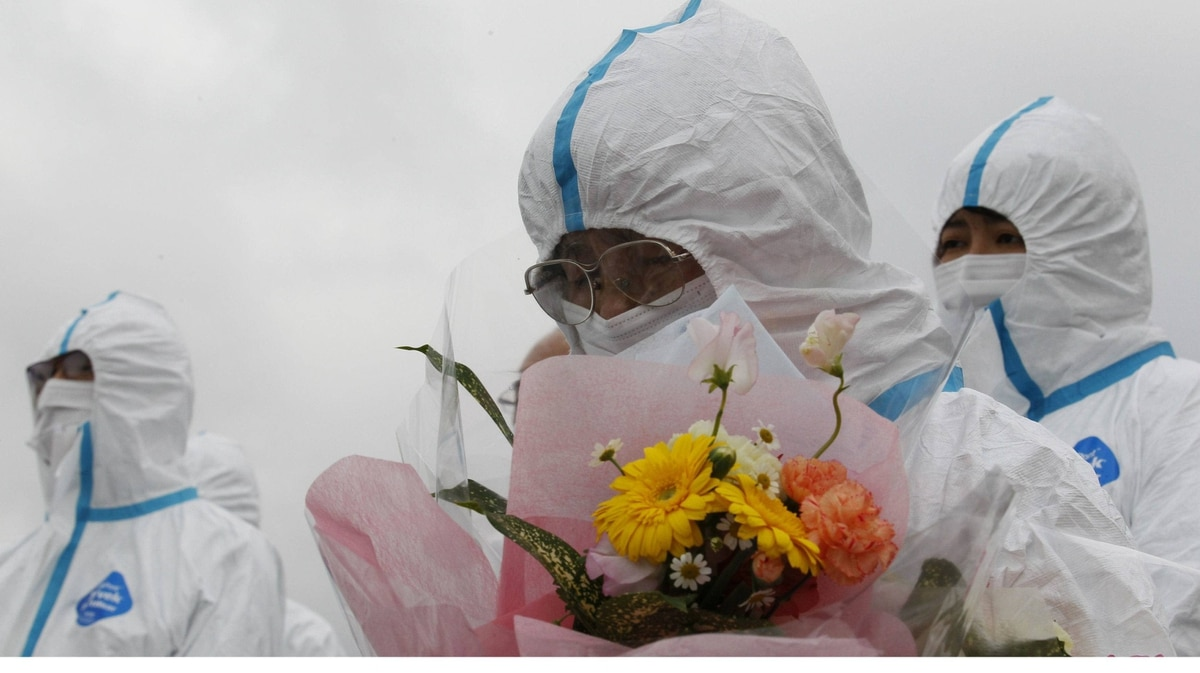 Tomoe Kimura is an evacuee of Okuma town, Fukushima prefecture, who lost her grandchild in the 2011 tsunami. She wears a white protective suit and holds flowers as she offers prayers for the victims in the 20-kilometre exclusion zone that now includes Okuma on Sunday.