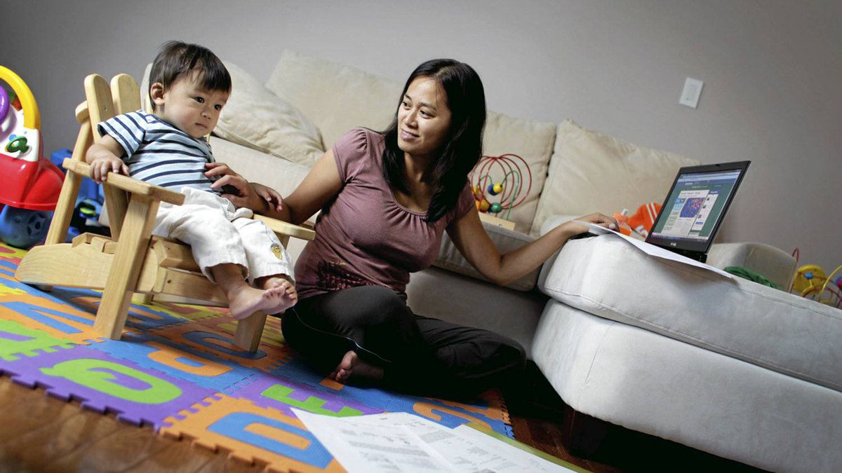 Stay-at-home mom, Samantha Li, sits with her 15-month old son, Emmett Li, while printing out some daily deal coupons at home in Toronto on Oct. 5, 2010. (Photo by Peter Power/The Globe and Mail)pmp
