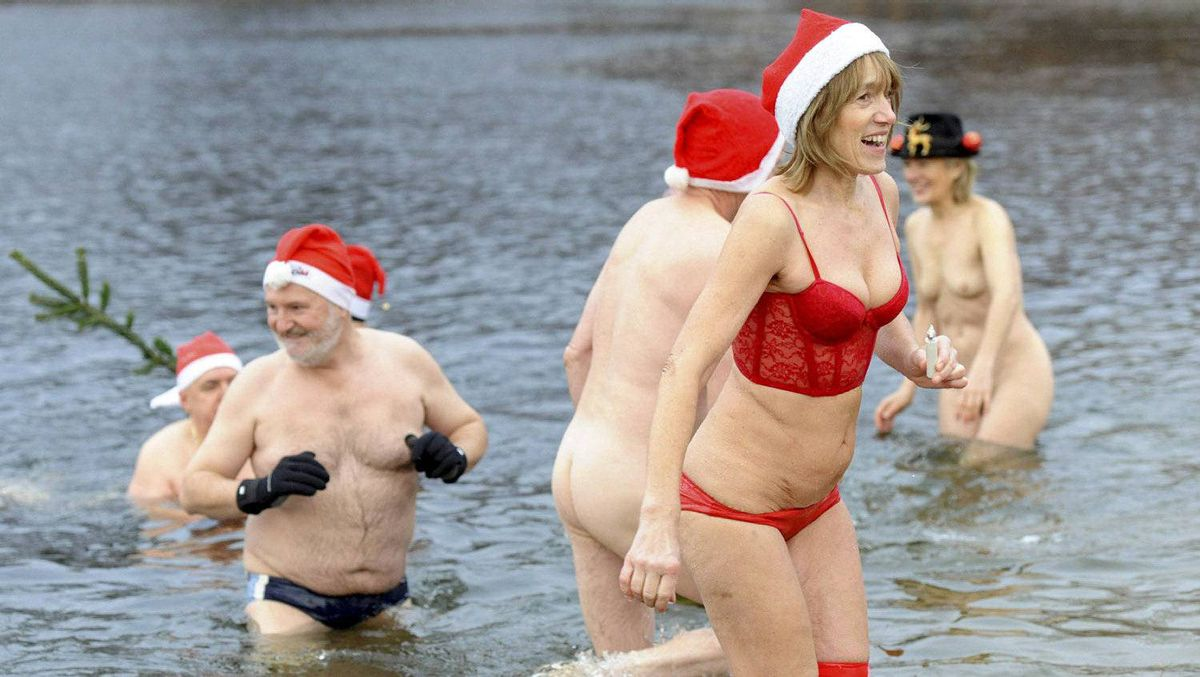 """Members of Berlin's swimming club """"Berliner Seehunde"""" (Berlin Seals) take a dip in the Orankesee lake during their traditional Christmas ice swimming session in Berlin on December 25, 2011."""