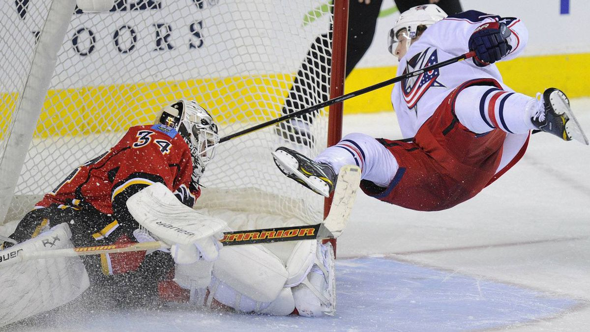 Columbus Blue Jackets' Cam Atkinson (R) goes flying through the air after he scored the game-winning goal on Calgary Flames goalie Miikka Kiprusoff in a shootout during their NHL game in Calgary, Alberta March 18, 2012. REUTERS/Todd Korol