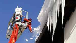 A worker uses an ice axe to remove snow and icicles from a roof of a building in Davos.