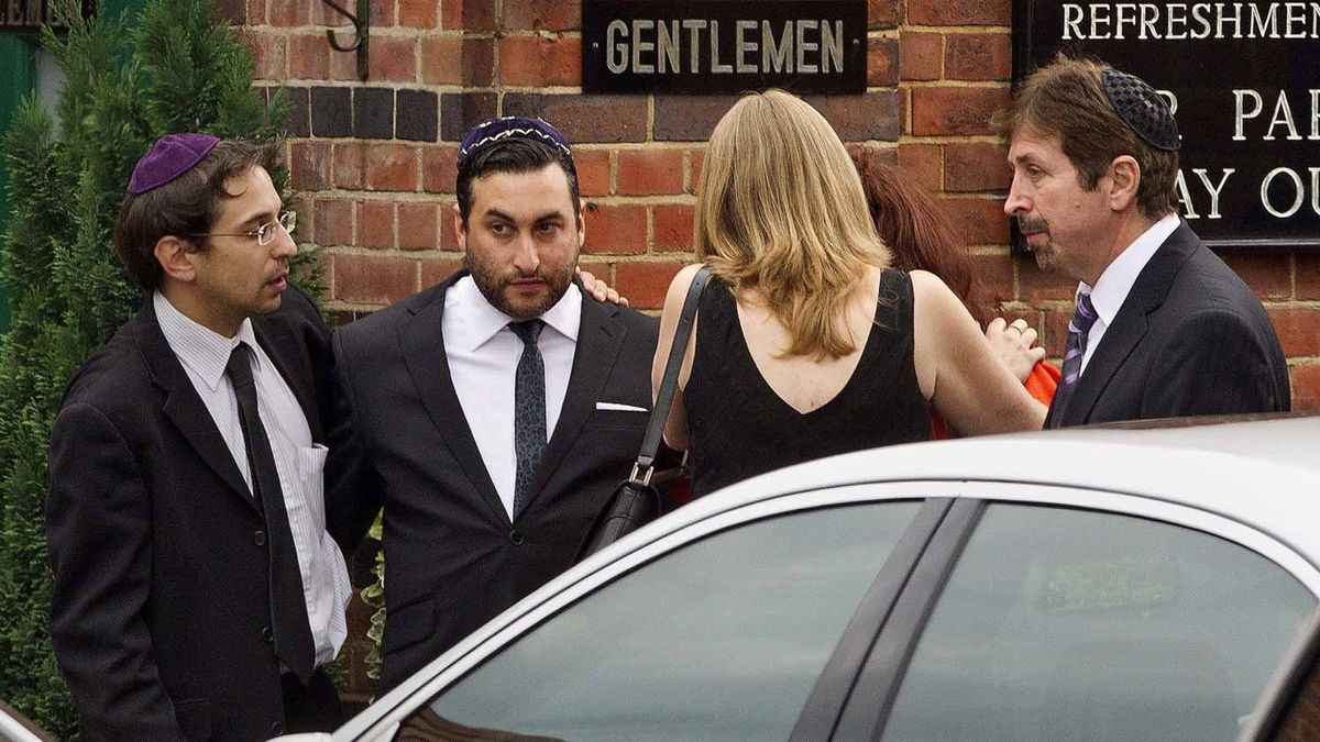 British singer Amy Winehouse's brother Alex, second from left, is consoled by unidentified people as he arrives at Golders Green Crematorium for the funeral ceremony of his sister, north London, Tuesday, July 26, 2011.