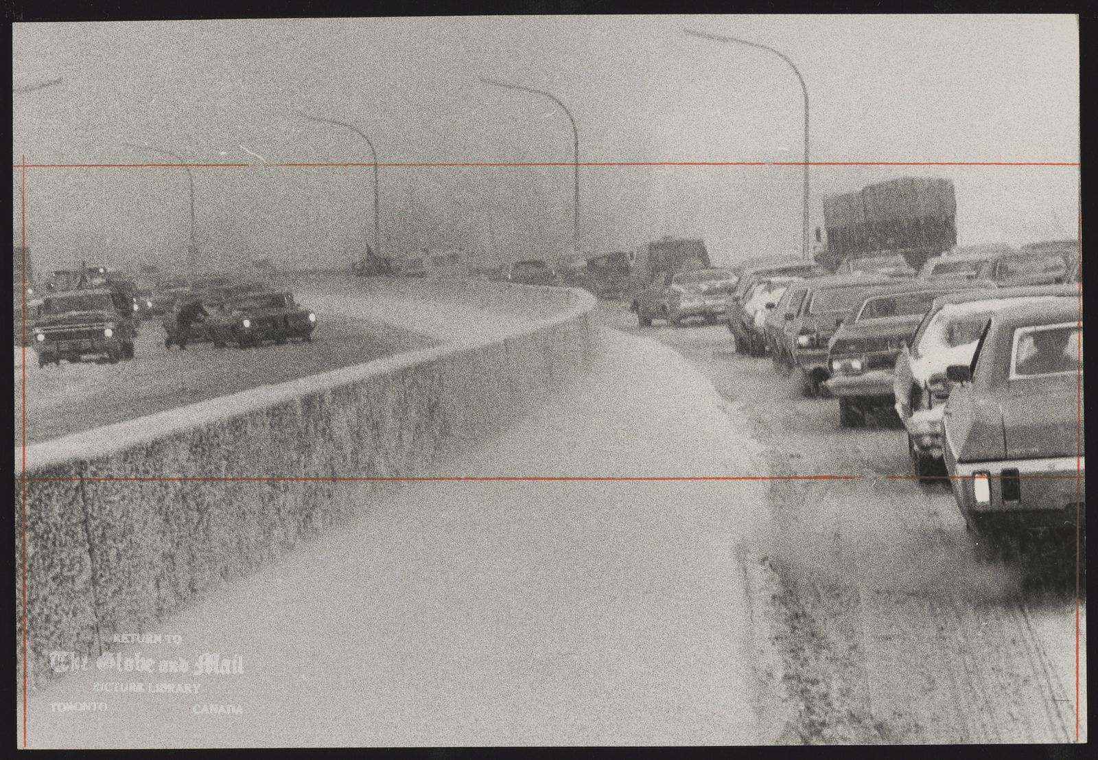 The notes transcribed from the back of this photograph are as follows: On the Don Valley Parkway, before it was closed to traffic on Saturday, cars and trucks crawled north and south with some cars needing a push or tow.