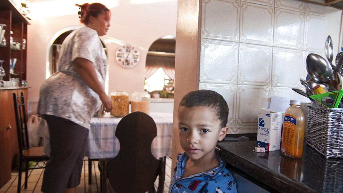 Anastasia Thomas sets out cereal while son Ethan, 5, waits to eat. The civil servant is up by 5:30 a.m. to make sure her kids get their baths and breakfast.