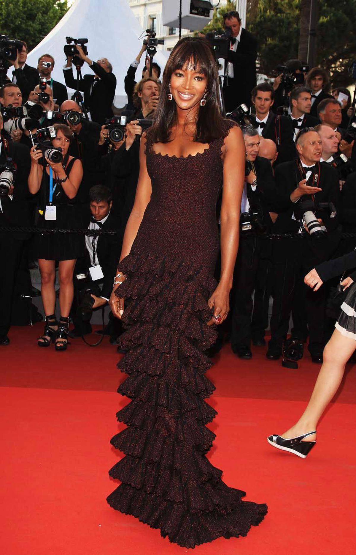 """Naomi Campbell poses on the red carpet at the """"The Beaver"""" premiere at the Cannes Film Festival on Tueday. That rude leg you see surging into the photo on the right was later brutally ripped off and used to beat its incautious owner about the head."""