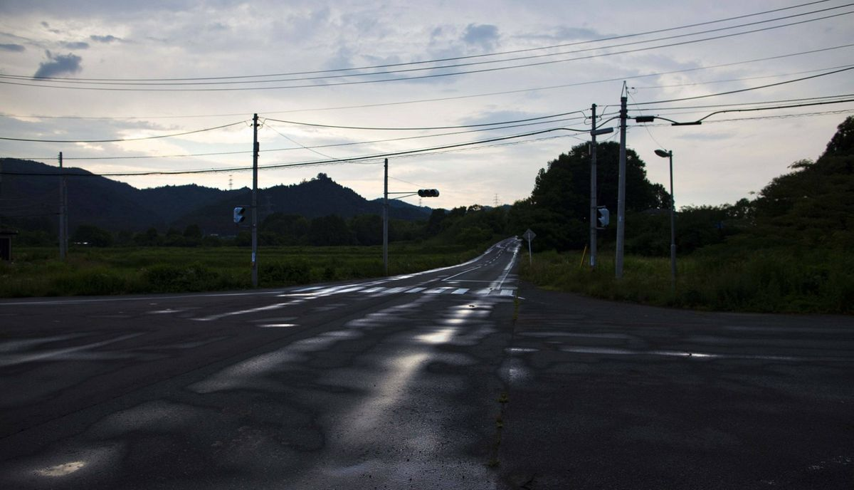 An abandoned street stretches through the town of Naraha, inside the 20-kilometer exclusion zone around the Fukushima Dai-ichi nuclear plant July 10, 2011. A year after the Tsunami, cleanup has begun, but experts say areas inside the nuclear exclusion zone will be difficult to decontaminate.