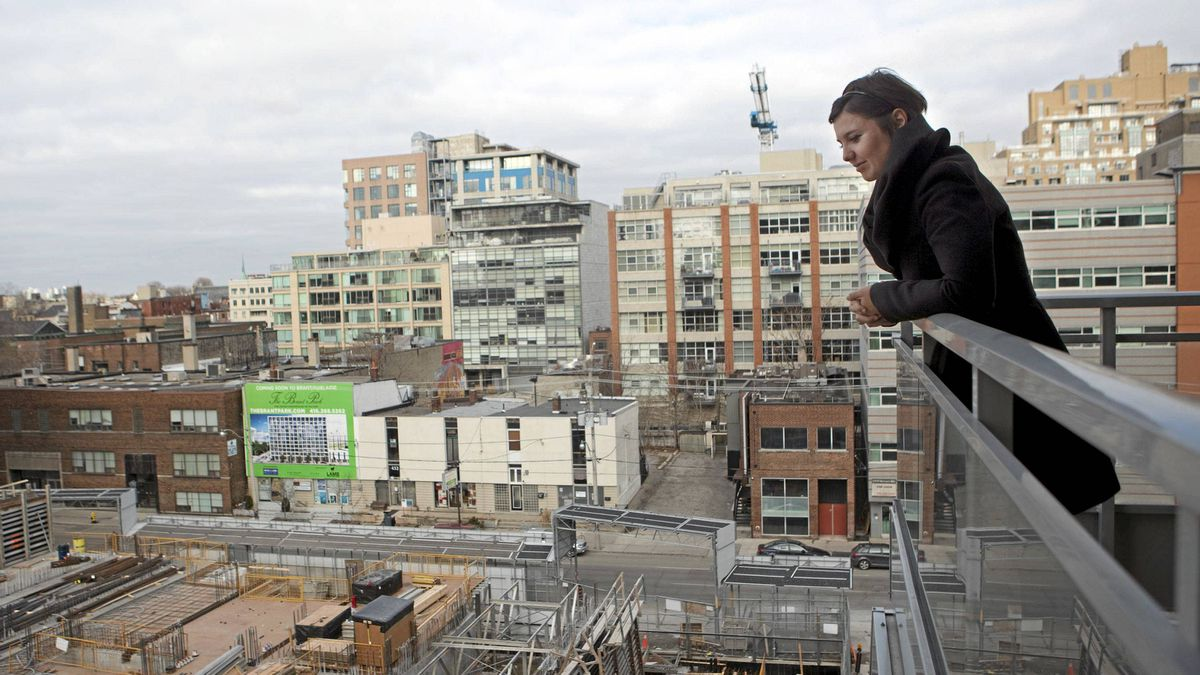 Condo owner Eva Kanovich looks onto a neighbouring condo under construction from her balcony in downtown Toronto on Feb. 4, 2012.