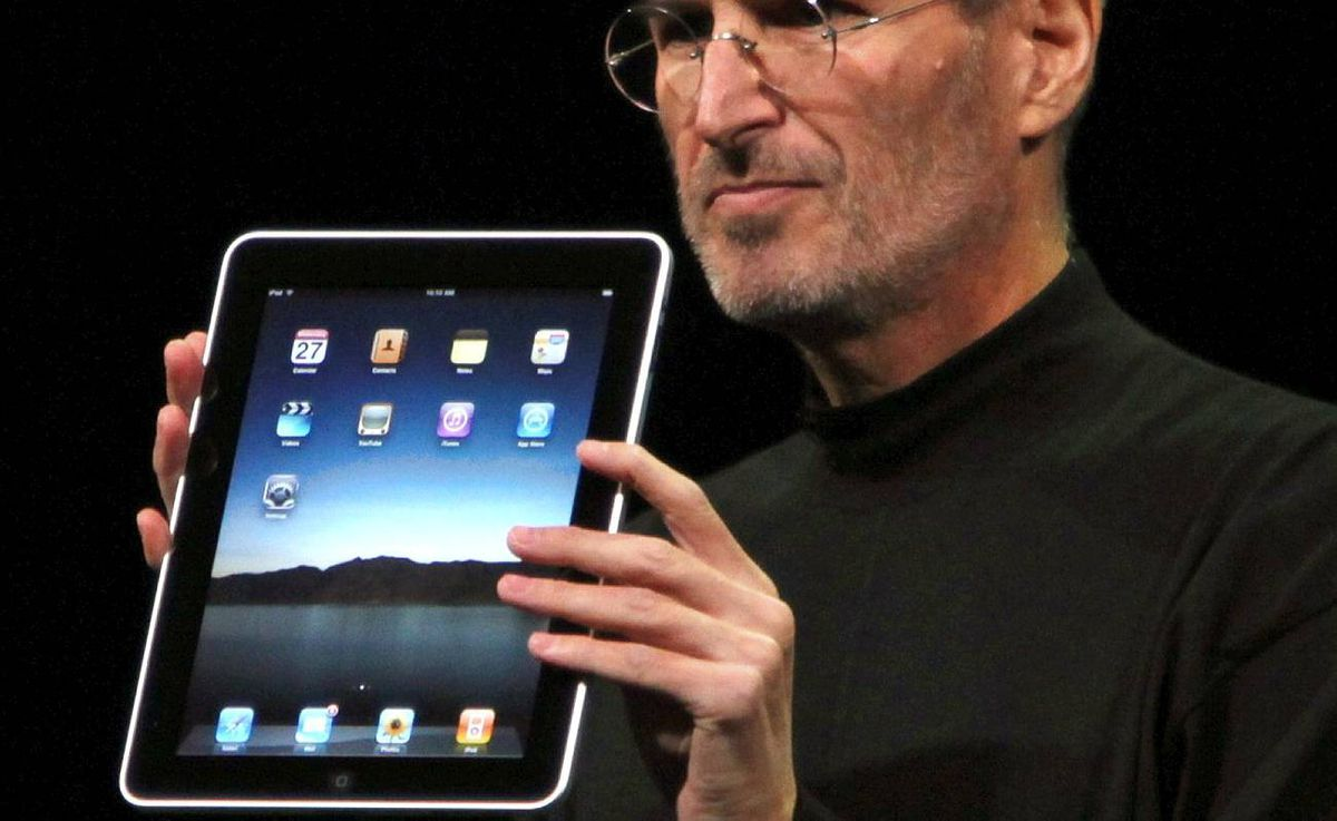 """Apple Chief Executive Officer Steve Jobs holds the new """" iPad"""" during the launch of Apple's new tablet computing device in San Francisco, California."""