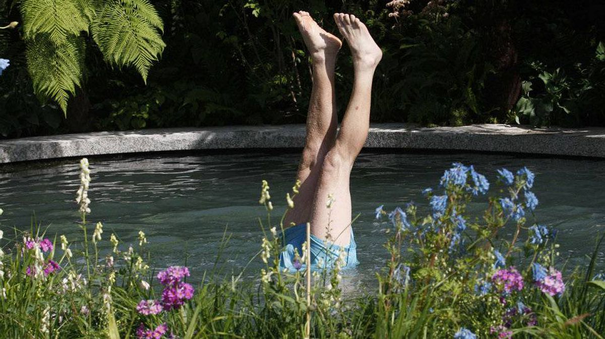 Worker Matt Attwood looks for stones on the floor of the pool in the Homebase garden display ahead of the Monday opening of the Chelsea Flower Show 2011, in London May 21, 2011.