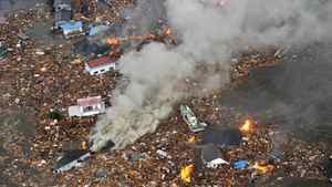 Flames rise from houses and debris half submerged by a tsunami in Sendai, northeastern Japan. Kyodo News/AP