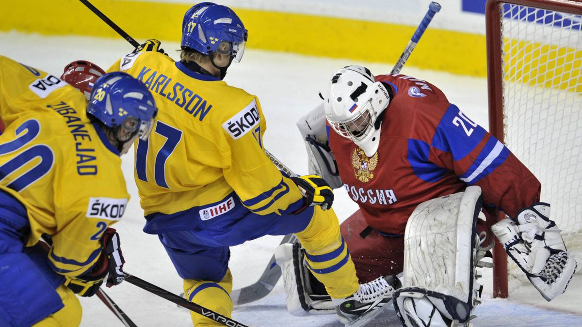 Russia goaltender Andrei Makarov holds his ice as Sweden's William Karlsson crashes his crease.