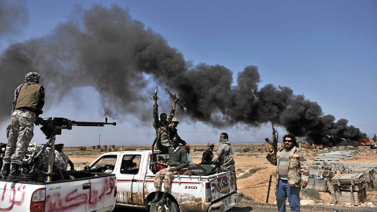 Smoke billows as Libyan rebels progress westward from the town of Bin Jawad towards Moammar Gadhafi's hom town of Sirte on March 28, 2011.