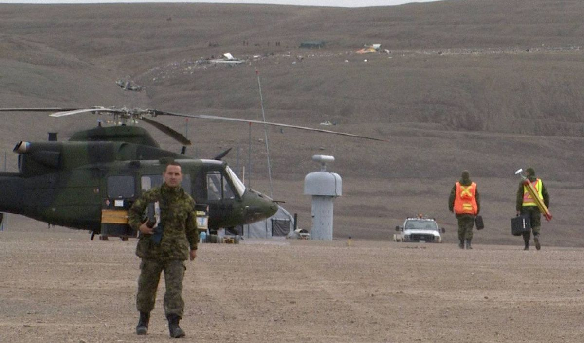 Military personnel work near the scene of the First Air crash site (background) in Resolute Bay, Nunavut on Sunday Aug. 21, 2011.