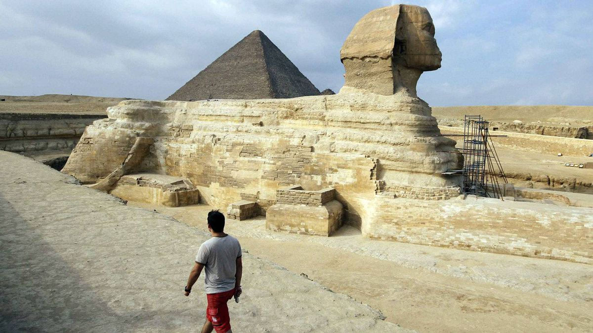 A tourist walks in front of the Great Giza pyramids on the outskirts of Cairo.