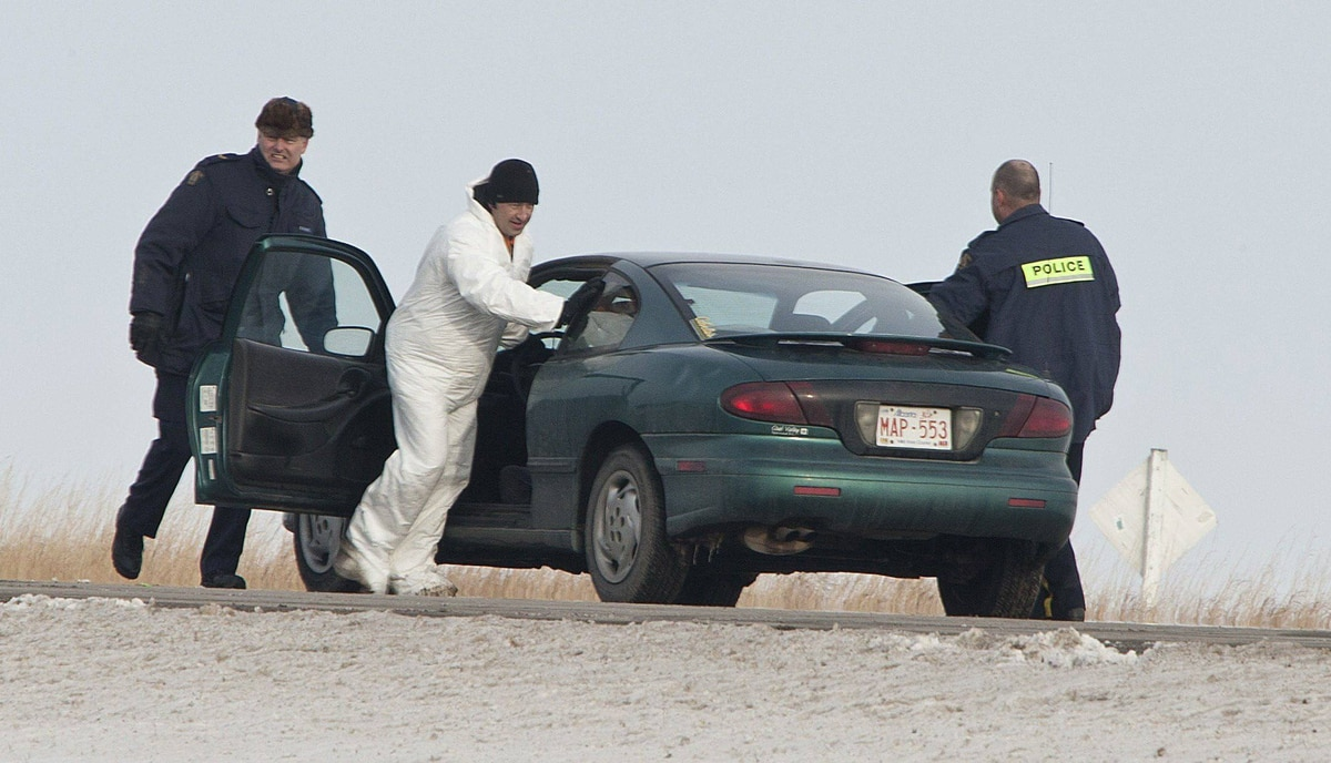 RCMP examine a car at the side of Highway #2, 130 kms south of Calgary after two bodies were discovered and two others were taken to hospital in critical condition early this moring.