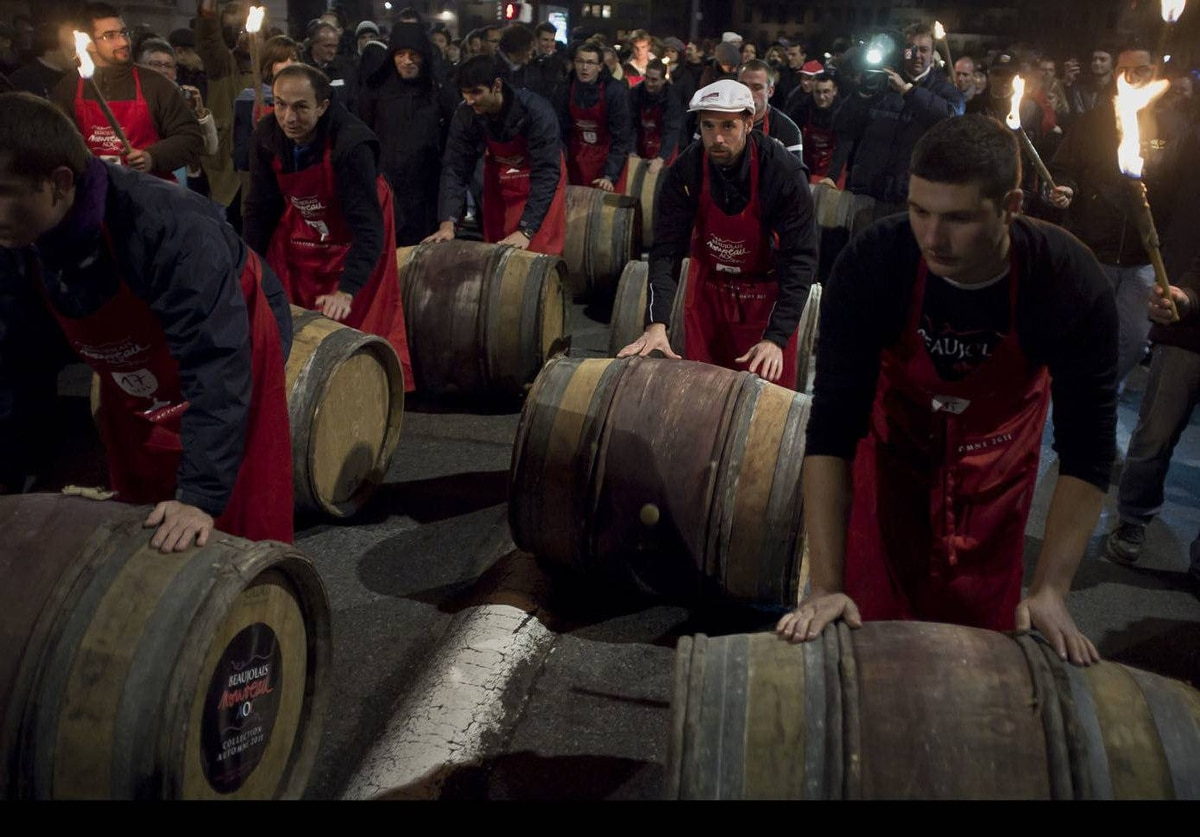 Barrels of Beaujolais Nouveau wine are rolled by wine-growers in the center of Lyon, France, during the 2011 vintage Beaujolais Nouveau launch.