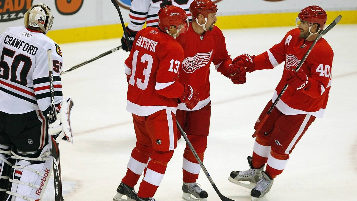 Tomas Holmstrom #96 of the Detroit Red Wings celebrates a first period goal with Pavel Datsyuk and Henrik Zetterberg #40 during a pre season game on September 24, 2010 at Joe Louis Arena in Detroit, Michigan. (Photo by Gregory Shamus/Getty Images)