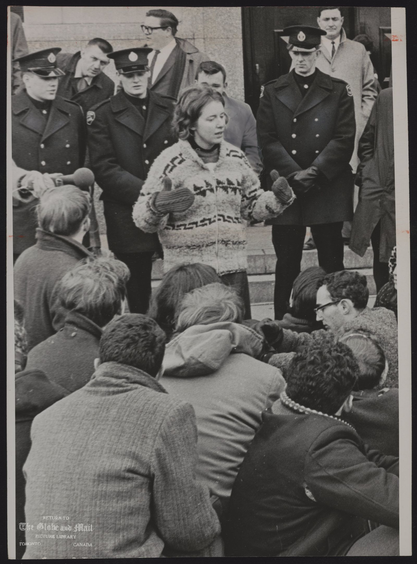 The notes transcribed from the back of this photograph are as follows: DEMONSTRATIONS Racial Jill Answeiler, first year student at New College and spokesman for the demonstrators addresses them after their ejection from the consulate by police. She was removed next to last. (U.S. Consulate, University Ave. Tor)