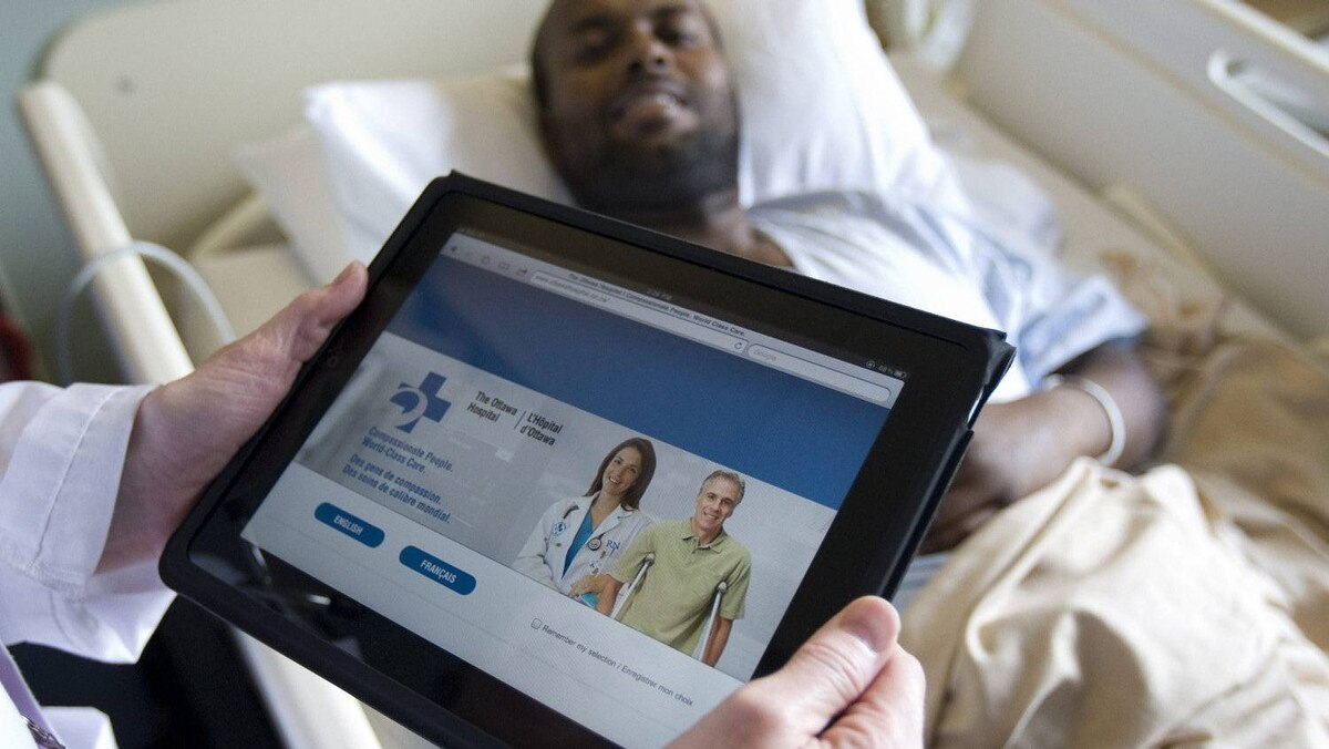 A doctor at Ottawa Hospital uses an iPad while seeing a patient in June, 2011.