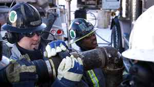Workers assemble a high-pressure pipe at a hydraulic fracturing operation near Bowden, Alta.