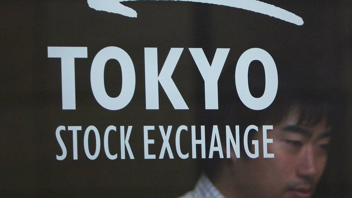 A man is seen behind a logo of the Tokyo Stock Exchange (TSE) as he walks out from the bourse in Tokyo July 6, 2011.