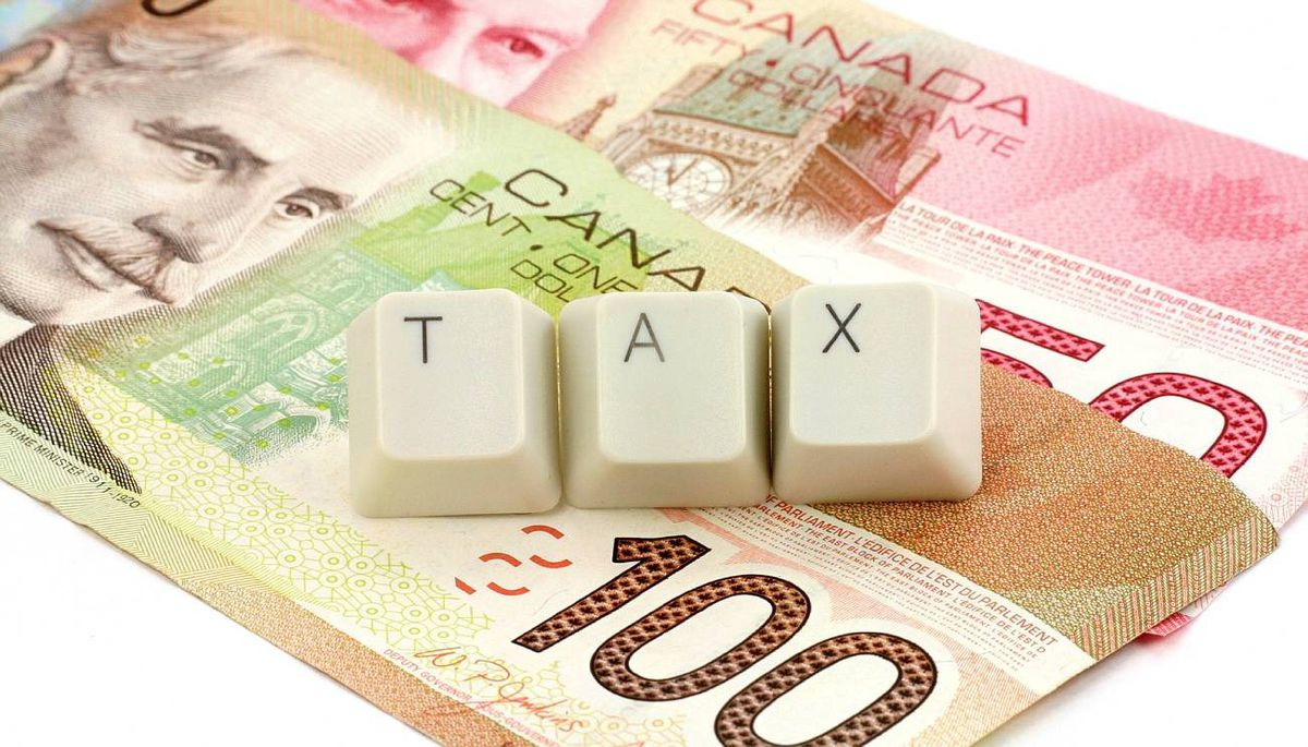 canadian dollar and computere keys, concept of tax. iStockphoto