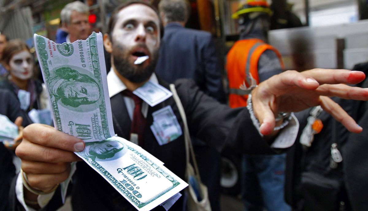 """A demonstrator holds play money while dressed as a """"corporate zombie"""" as he walks with others taking part in an Occupy Wall Street protest in lower Manhattan in New York, October 3, 2011. The Occupy Wall Street protests moved into their third week Monday with demonstrators camping out in Zuccotti Park."""