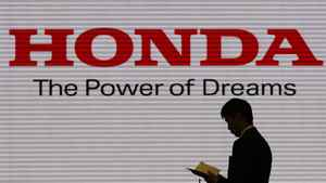 A man is silhouetted against a logo of Honda Motor at the company showroom in Tokyo January 31, 2012.