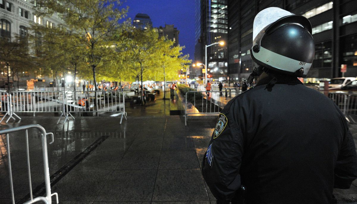 A New York Police Department officer watches sanitation crews clean Zuccotti Park after city officials evicted the 'Occupy Wall Street' protest from the park in the early morning hours of November 15, 2011 in New York.