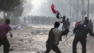 Egyptian protesters threw rocks and firebombs at military police as another waves a national flag during clashes near Cairo's downtown Tahrir Square, Egypt Friday, Dec. 16, 2011.