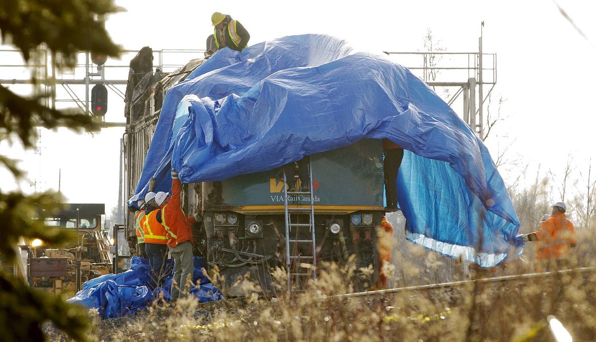 BURLINGTON, ONT. - Feb. 28, 2012 - The Via locomotive that derailed on Feb 26, 2012, is covered by a tarp and removed form the scene in Burlington on Feb. 28, 2012. Crews dragged it up to the tracks at about 2pm and uprighted it once again. Only one track remains closed while the work is being done, and the locomotive is expected to be removed by early on Tuesday afternoon. The Via passenger train, enroute from Niagara Falls to Toronto, derailed on Sunday at approximately 3:30pm. Three VIA employees in the engine died as a result if the crash, and many passengers were taken to local hospitals; three with serious injuries. One track has been open and trains have been passing the site all day. (Photo by Peter Power/The Globe and Mail)pmp