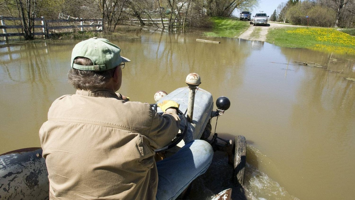 Robin Carter drives his tractor beside his home along the intentional breach of the dike along the Assiniboine River Monday, May 16, 2011 in Manitoba.
