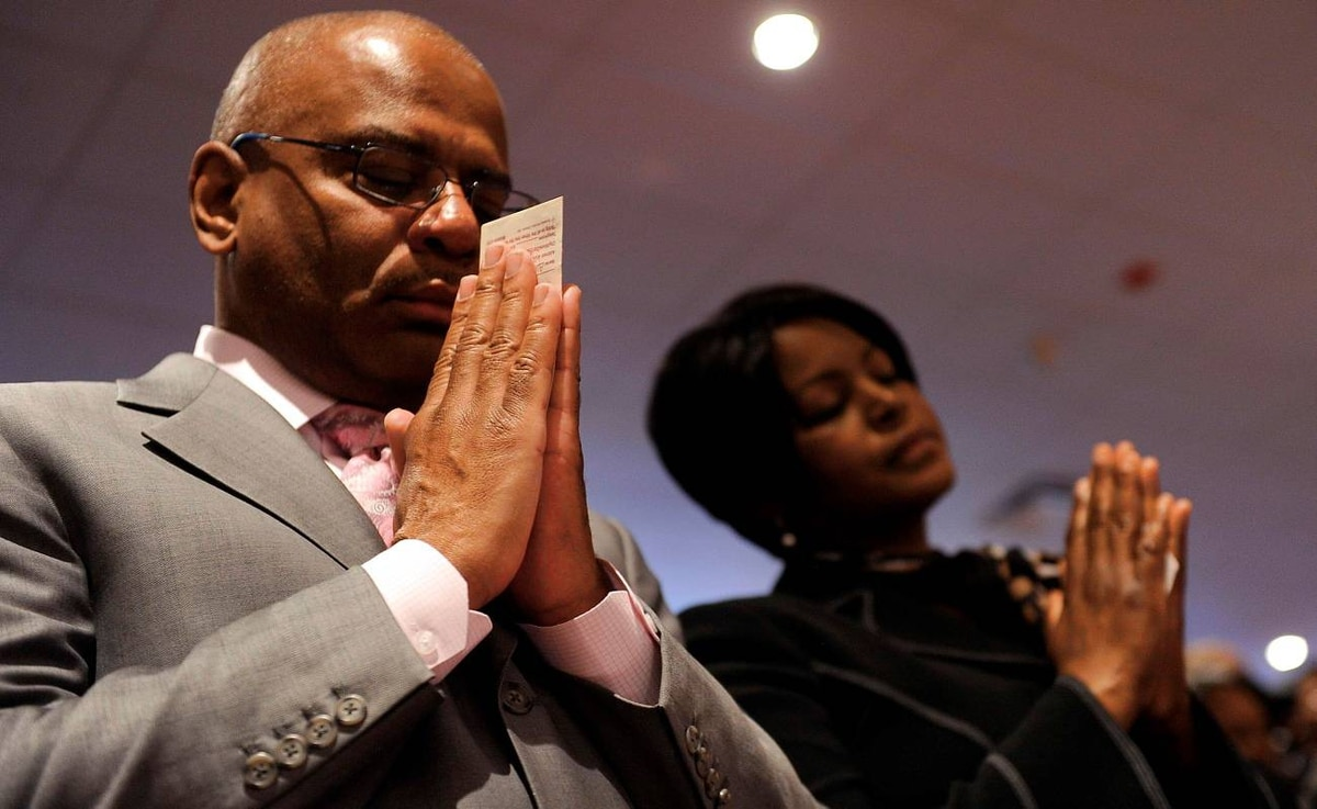 Parishioners hold their offering envelopes and say a pray of thanks for their life's blessings during a Sunday morning worship service at Ebenezer AME Church in Fort Washington, Maryland