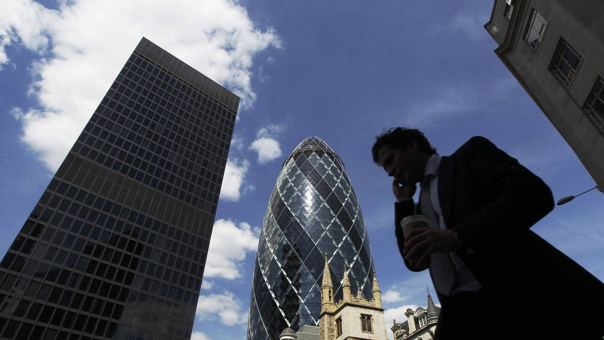 A man passes the Swiss RE building, also known as the Gherkin, in the financial district City of London June 22, 2010.