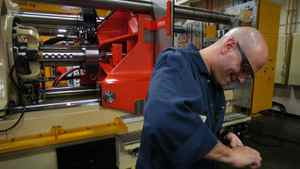 A worker is seen assembling an injection molding machine at a Husky Injection Molding Systems plant in Bolton, Ont., in a November 2005 file photo.