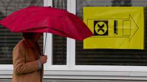 A woman carries an umbrella as she enters a polling station to vote in the federal election in Sidney, B.C., on Vancouver Island, on Monday May 2, 2011.