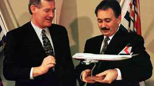 Airlines' president Kevin Benson gives British Columbia Premier Glen Clark (R) a model of a Canadian Airlines Boeing 747 as a gift, November 29, 1996 in Vancouver after the Premier announced his government would be giving the cash strapped airline financial support.