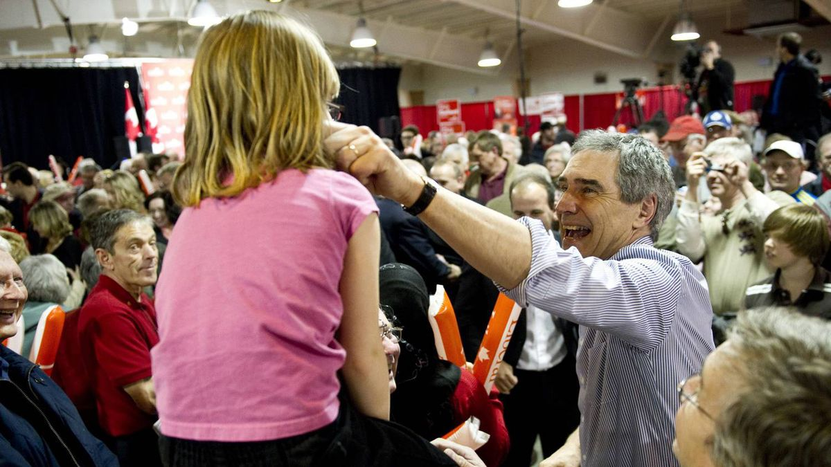 Michael Ignatieff pinches a young girl's cheek as she sits on the father's shoulders during a rally Saturday, April 23, 2011