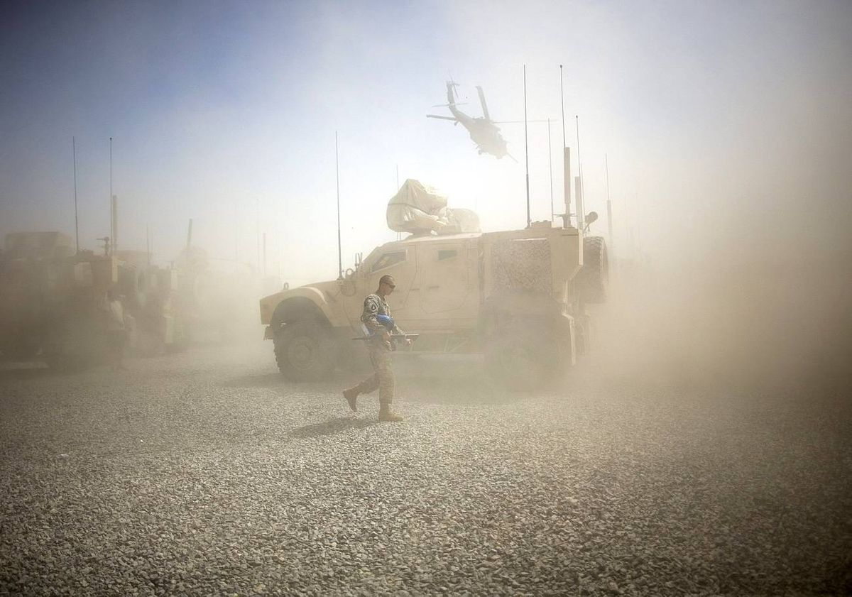 A U.S. Army soldier takes cover from dust whipped up by a departing helicopter at Combat Outpost Terra Nova in Kandahar, Afghanista.
