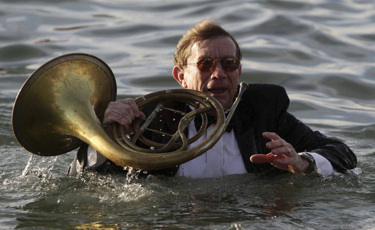 Dressed in a tuxedo and holding a French horn, Ken Petry takes a dip in the frigid waters of English Bay during the 91st annual Polar Bear Swim in Vancouver, B.C., on Saturday January 1, 2011.
