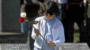 A child holds a flower that will be placed on a grave marker at a memorial service at Fairview Lawn Cemetery to mark the 100th anniversary of the sinking of RMS Titanic in Halifax on Sunday, April 15, 2011.