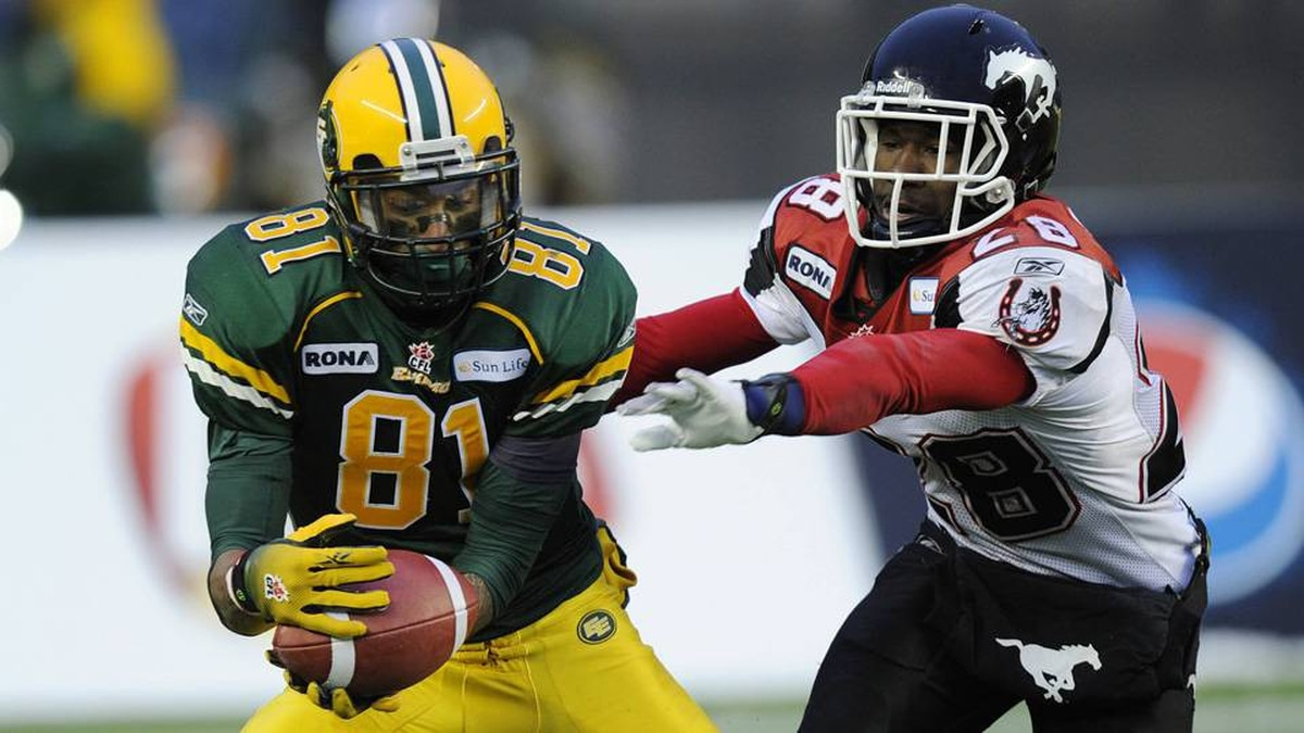 Edmonton Eskimos' Jason Barnes (L) catches a touchdown pass in front of Calgary Stampeders' Brandon Smith during the first half of their semi-final CFL football game in Calgary, Alberta, November 13, 2011.
