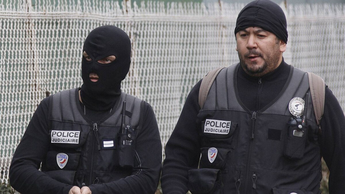 Police officers stand near a building in Toulouse, France, Wednesday March 21, 2012 where a suspect in the shooting at the Ozar Hatorah Jewish school is barricaded in an apartment building.