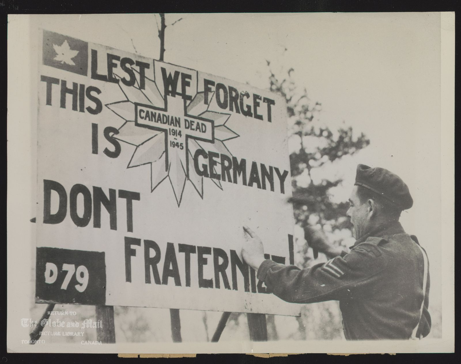 REMINDING ALLIES THEY ARE ON ENEMY SOIL. CPL. E.A. NAULT (ABOVE), OF MEADOW LAKE, SASKATOON, CANADA, PUTS UP A SIGN ALONG THE ROAD TO CALCAR, GERMANY, REMINDING ALLIED TROOPS THAT THEY ARE ON ENEMY SOIL AND WARNING THEM AGAINST FRATERNIZING WITH THE ENEMY. 3-7-45 [1945]