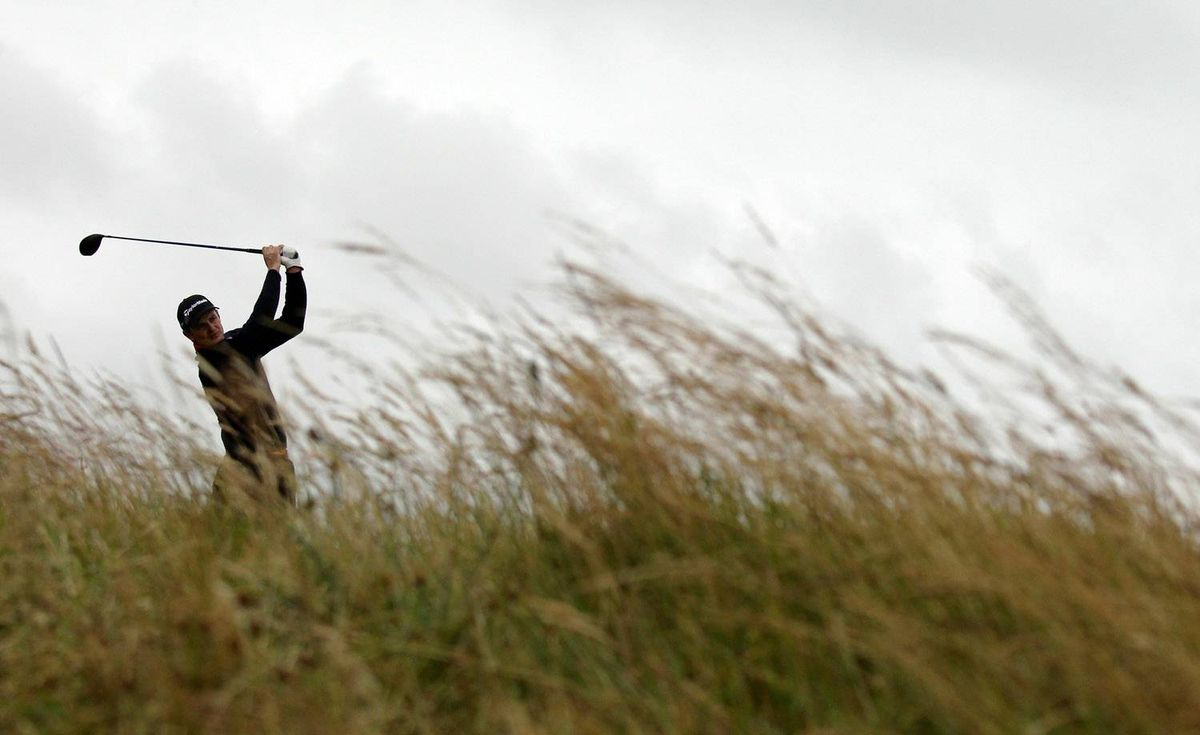 Justin Rose practices in the wind and rain at the Old Course, St. Andrews on Wednesday